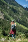 Young happy woman with backpack standing on a rock with raised hands and looking to a valley below.  stock photography