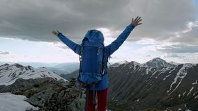 Young happy woman with backpack standing on a rock with raised hands and looking to a valley below stock video footage