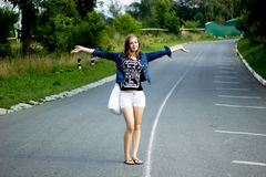 Young happy woman with a bag on a road Stock Photos