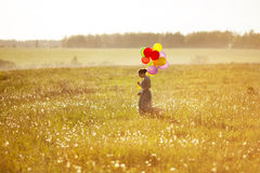 Young happy woman with balloons in a field. Of dandelions Royalty Free Stock Image