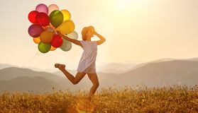 Happy woman with balloons at sunset in summer royalty free stock images