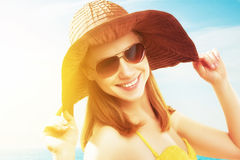 Young happy woman on the beach in  sunglasses and a hat Royalty Free Stock Photography