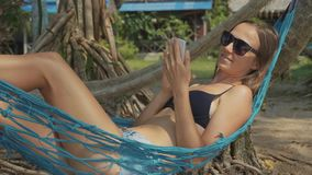 Young woman lying on hammock with smart phone at the sandy beach in slow motion stock footage