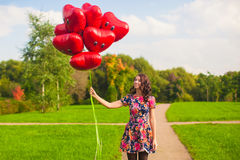 Young happy woman in beautiful dress with red balloons walking outside Stock Images