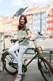 Young happy woman on bicycle  smiling at camera. Young happy woman on bicycle looking at camera at the Nyhavn harbor pier in european city Copenhagen, Denmark Stock Image