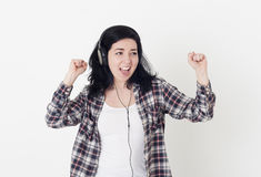 Young happy woman in a big headphones sings his favorite song and dance against a white wall Royalty Free Stock Photography