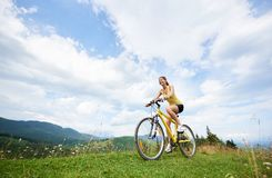 Attractive female cyclist with yellow mountain bicycle, enjoying sunny day in the mountains. Young happy woman biker cycling on yellow mountain bicycle on a stock photo
