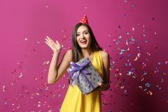 Young woman with birthday gift on color background royalty free stock images