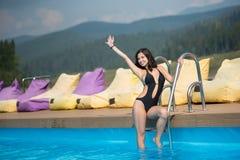 Young happy woman in black bikini is posing in the swimming pool on mountain resort Royalty Free Stock Photos