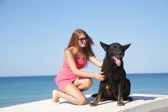 Young happy woman with black dog Stock Photo