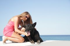 Young happy woman with black dog Royalty Free Stock Image