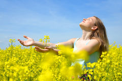 Young happy woman on blooming rapeseed field Royalty Free Stock Images