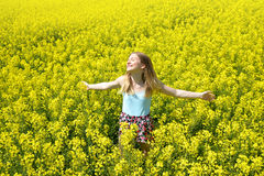 Young happy woman on blooming rapeseed field Stock Photo