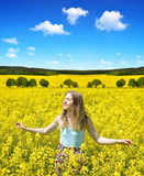 Young happy woman on blooming rapeseed field Stock Images