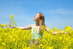 Young happy woman on blooming rapeseed field. In spring Stock Photography