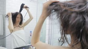 Young happy woman blow drying hair in bathroom, lifestyle. Hair style beauty concept. Young happy woman blow drying hair in bathroom, lifestyle. Hair style stock video footage