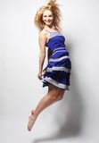 Young happy woman in blue dress jumping Royalty Free Stock Photos