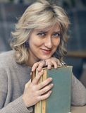 Young happy woman with a book. Smiling looking at the camera Royalty Free Stock Photography