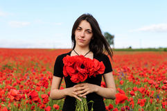 Young happy woman with a bouquet of red poppies Stock Photo