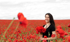 Young happy woman with a bouquet of red poppies Royalty Free Stock Images