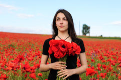 Young happy woman with a bouquet of red poppies Royalty Free Stock Photography