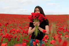 Young happy woman with a bouquet of red poppies Royalty Free Stock Image