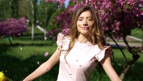 Young happy woman with bouquet of tulips. Young happy playful woman with bouquet of tulips among flowering garden. Petals falls from trees stock video