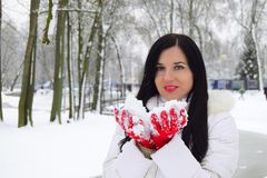 The young, happy woman the brunette holds snow in hand. The woman is dressed in red gloves and a white coat. The woman is in the winter park Stock Photo