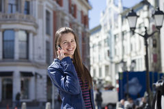 Young happy woman calling by phone on the street Royalty Free Stock Image