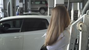 Young happy woman in car service throwing up her car keys and smiling and cheering on the background of her car stock footage
