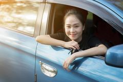 Young happy woman in car with sunlight Stock Photo
