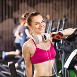 Young happy woman at cardio area in fitness center. Young happy woman with headphones on cardio training in fitness center. Smiling beautiful girl doing exercise Royalty Free Stock Photos