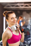 Young happy woman at cardio area in fitness center. Young happy woman with headphones on cardio training in fitness center. Smiling beautiful girl doing exercise Royalty Free Stock Image