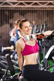 Young happy woman at cardio area in fitness center Stock Photo