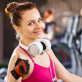 Young happy woman at cardio area in fitness center. Young happy woman with headphones on cardio training in fitness center. Smiling beautiful girl showing thumbs Royalty Free Stock Image