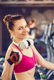 Young happy woman at cardio area in fitness center. Young happy woman with headphones on cardio training in fitness center. Smiling beautiful girl showing thumbs Stock Images