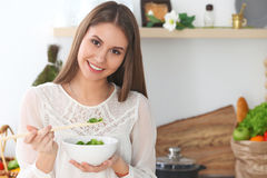 Young happy woman is cooking or eating fresh salad in the kitchen. Food and health concept Stock Photography
