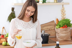 Young happy woman is cooking or eating fresh salad in the kitchen. Food and health concept Stock Image