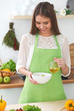 Young happy woman is cooking or eating fresh salad in the kitchen. Food and health concept Royalty Free Stock Images