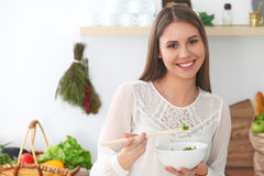 Young happy woman is cooking or eating fresh salad in the kitchen. Food and health concept Stock Photo