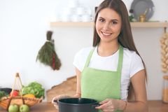 Young happy woman cooking in the kitchen. Healthy meal, lifestyle and culinary concept.  Stock Photos