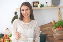 Young happy woman cooking in the kitchen. Healthy meal, lifestyle and culinary concept.  Stock Images