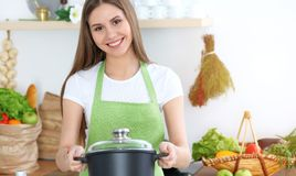 Young happy woman cooking soup in the kitchen. Healthy meal, lifestyle and culinary concept. Smiling student girl royalty free stock photo