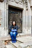 Young happy woman  at  Corvin Castle, Romania. Young happy woman   sitting near a  ancient door in a Gothic-Renaissance castle in Hunedoara Transylvania, Castle Royalty Free Stock Photos