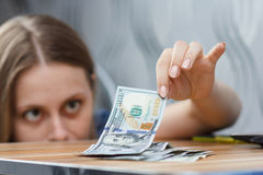 Young happy woman count dollars on the table Royalty Free Stock Photo