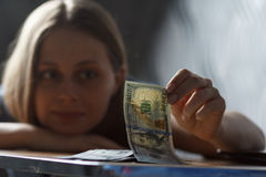 Young happy woman count dollars on the table Royalty Free Stock Images