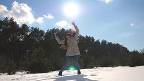 Young happy woman dances funny at the winter forest. Girl dance against the background of snowy landscape. Female stock footage