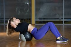 Young happy woman doing fitness exercises with fit ball at gym. Swing a press Stock Photography