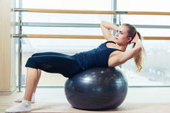 Young happy woman doing fitness exercises with fit ball at home Stock Photos