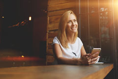 Young Happy Woman Dreaming About Something While Sitting With Smart Phone In Modern Coffee Shop Royalty Free Stock Photo